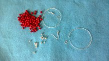 small silver and red beads, two circles of memory wire, two jump rings, and two fishhook ear wires
